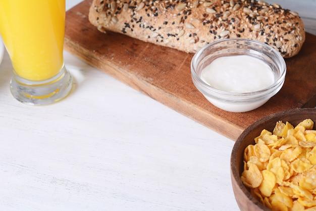 Kom ontbijtgranen, jus d'orange en toast met roomkaas