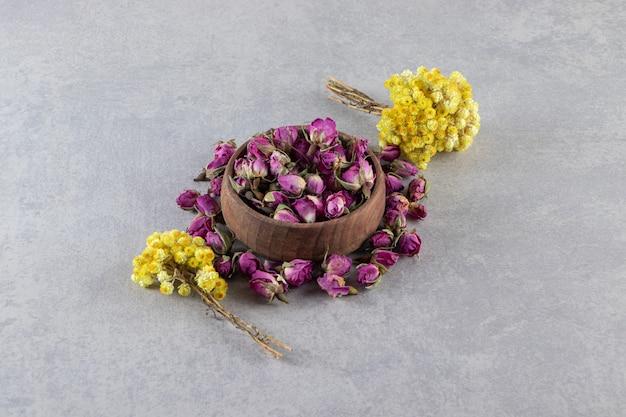 Kom ontluikende rozen en gele bloemen op stenen achtergrond.