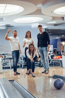Kom op, doe een staking. jonge, vrolijke vrienden vermaken zich in het weekend in de bowlingclub