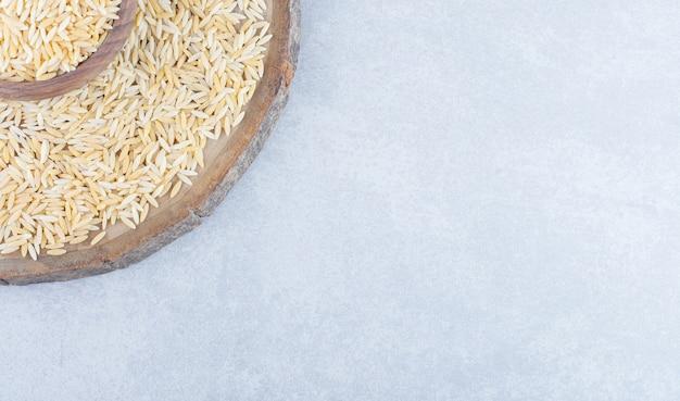 Kom op een houten bord, gevuld en omringd met een stapel bruine rijst op een marmeren oppervlak