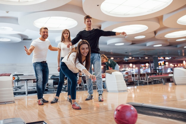 Kom op je kan het. jonge, vrolijke vrienden vermaken zich in het weekend in de bowlingclub
