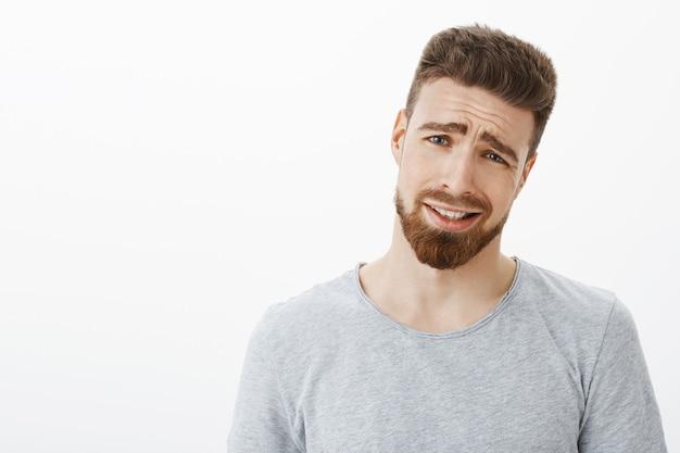 Kom op man, het is zwak. niet onder de indruk, ontevreden knappe zakenman met baard en blauwe ogen, kantelend hoofd en fronsende, turende en aanscherpende glimlach van ontevredenheid en onwil