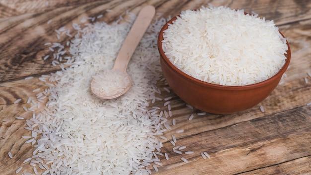 Kom organische witte rijst en houten lepel over geweven achtergrond