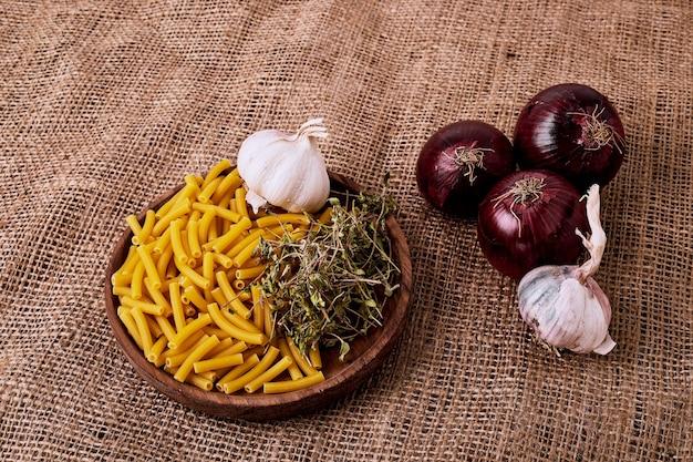 Kom pasta met uien en knoflook op bruine ondergrond.