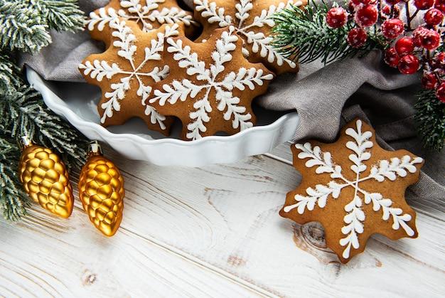 Kom peperkoek kerstkoekjes op rustieke witte houten tafel en groene spar tak. ruimte kopiëren.