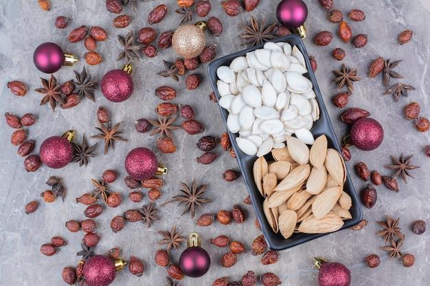 Kom pistache en pompoenpitten met rozenbottels en kerstballen.