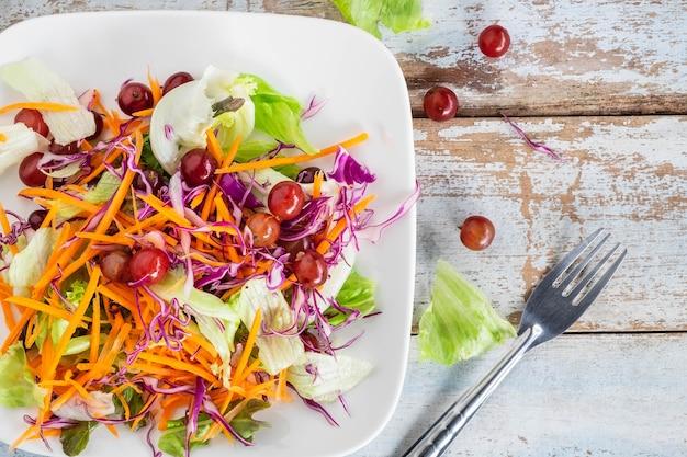 Kom plantaardige salade op houten lijst