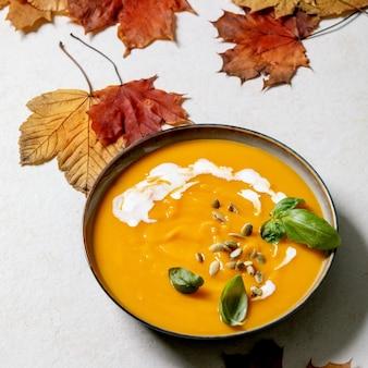Kom pompoen of wortel vegetarische roomsoep versierd met verse basilicum, room en pompoenpitten op een witte textuurachtergrond met gele herfst esdoornbladeren erboven. vierkante afbeelding