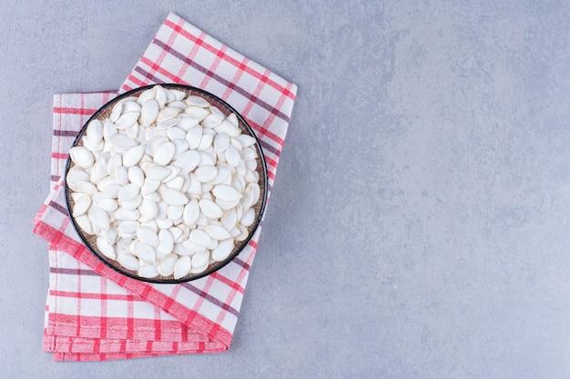Kom pompoenpitten op een theedoek, op het marmer.