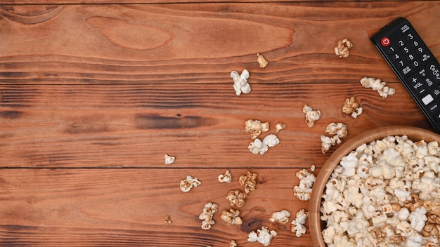 Kom popcorn en afstandsbediening op houten achtergrond.