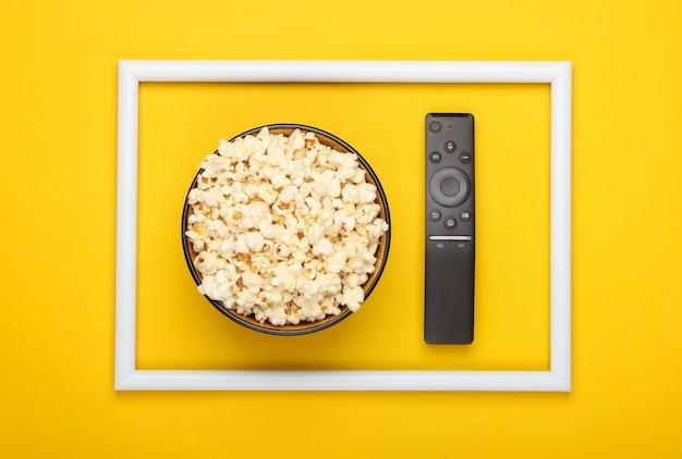 Kom popcorn en tv-afstandsbediening op geel oppervlak met wit frame