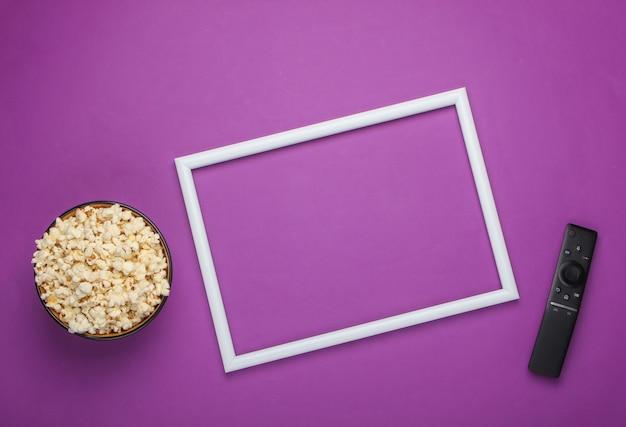 Kom popcorn en tv-afstandsbediening op paars oppervlak met wit frame