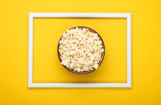 Kom popcorn op geel oppervlak met wit frame