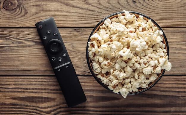 Kom popcorn, tv-afstandsbediening op wodden tafel.