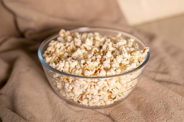 Kom popcorn voor het kijken naar een film op een beige bank, snacks en ongezond junkfoodconcept