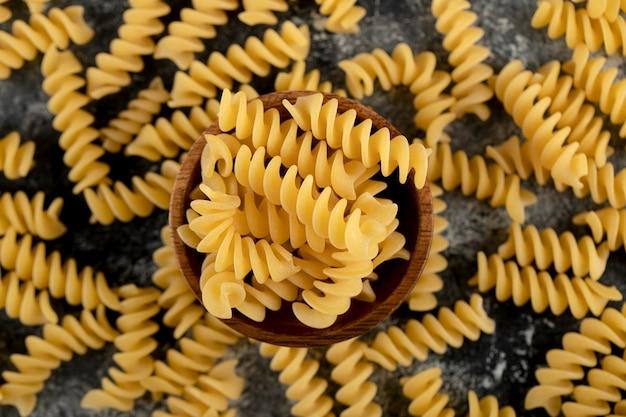 Kom rauwe fusilli pasta op marmeren oppervlak
