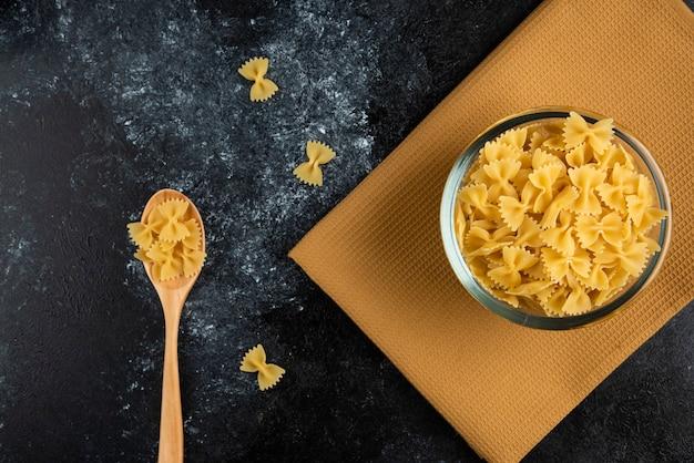 Kom rauwe pasta op tafellaken met lepel.