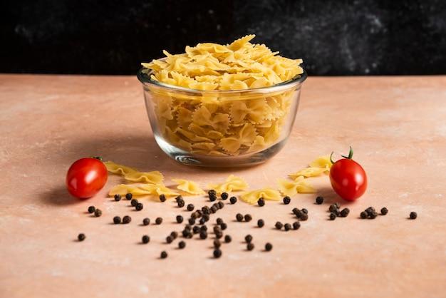 Kom rauwe pasta, peperkorrels en verse tomaten op oranje tafel.