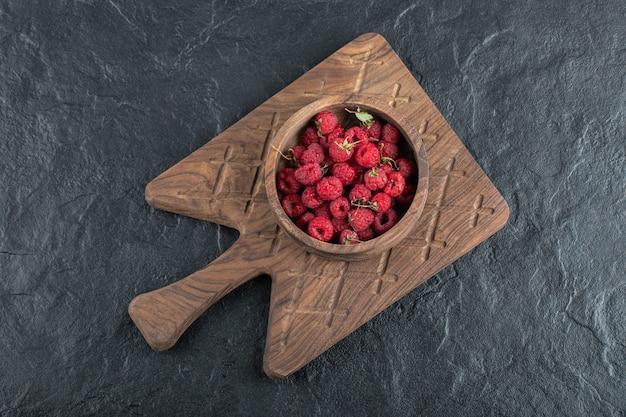Kom rijpe frambozen op een houten bord.