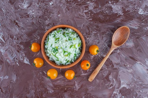 Kom rijst, tomaten en lepel op het marmeren oppervlak
