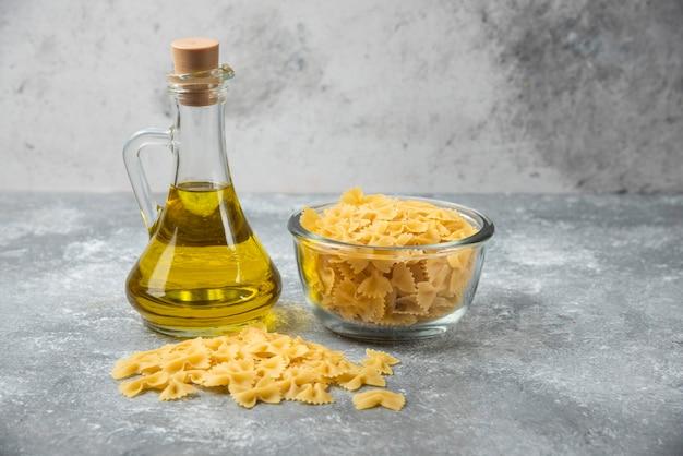 Kom ruwe farfalledeegwaren met fles olijfolie op marmeren achtergrond.