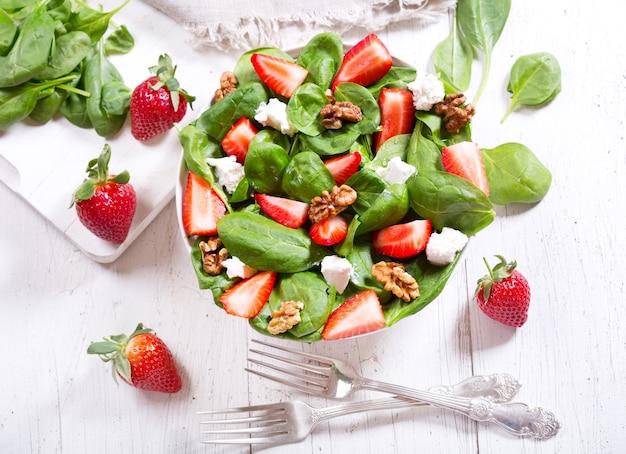 Kom salade met aardbei, spinazieblaadjes en fetakaas, bovenaanzicht