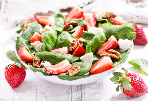 Kom salade met aardbei, spinazieblaadjes en fetakaas op houten tafel