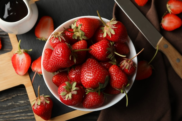 Kom smakelijke aardbeien op houten tafel
