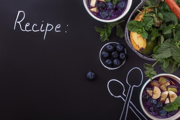 Kom smoothies met bessen op een bordachtergrond met lepels