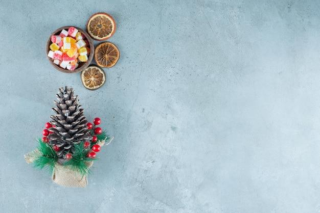 Kom snoepjes, gedroogde schijfjes citroen en een kerstversiering op marmer.