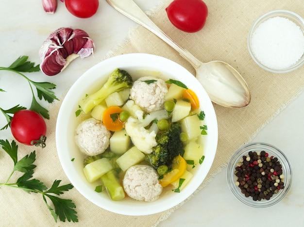 Kom soep, een kop bouillon en groenten, gehaktballen gemaakt van kalkoen en kip