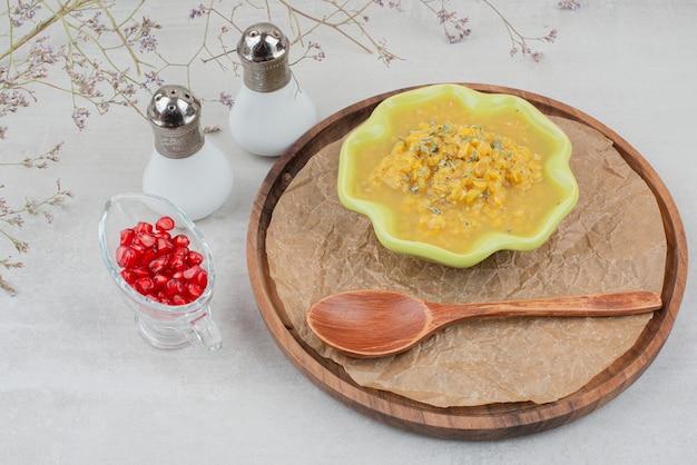 Kom soep op houten plaat met zout en granaatappelpitjes.