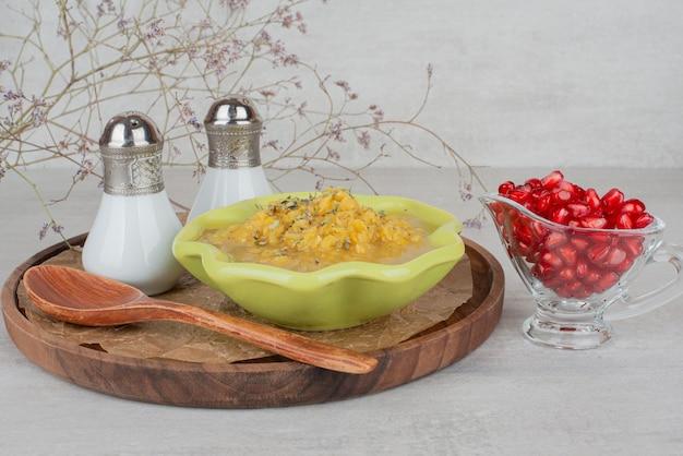 Kom soep, zout en granaatappelzaden op wit.