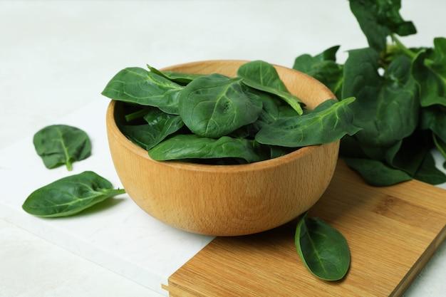 Kom spinazie aan boord, op een witte gestructureerde tafel