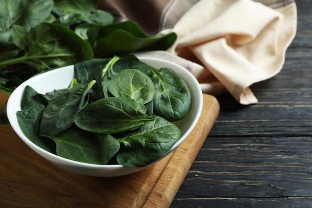 Kom spinazie op snijplank op houten tafel