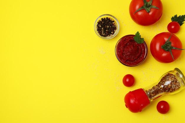 Kom tomatenpuree en ingrediënten op gele ondergrond, ruimte voor tekst