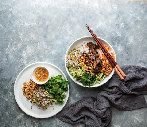 Kom traditionele vietnamese noedelsalade - bun bo nam bo, met rundvlees, rijstnoedels, verse kruiden, ingelegde groenten en vissaus