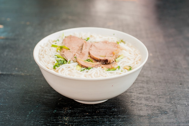 Kom traditionele vietnamese rundvlees soep pho bo op de donkere oude houten achtergrond