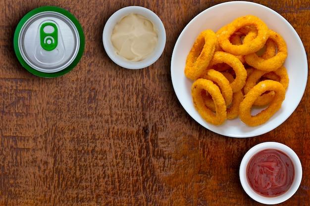 Kom uienringen met sauzen aan de zijkant en blikje frisdrank