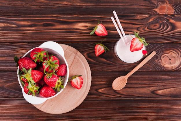 Kom van aardbeien en milkshake op tafel
