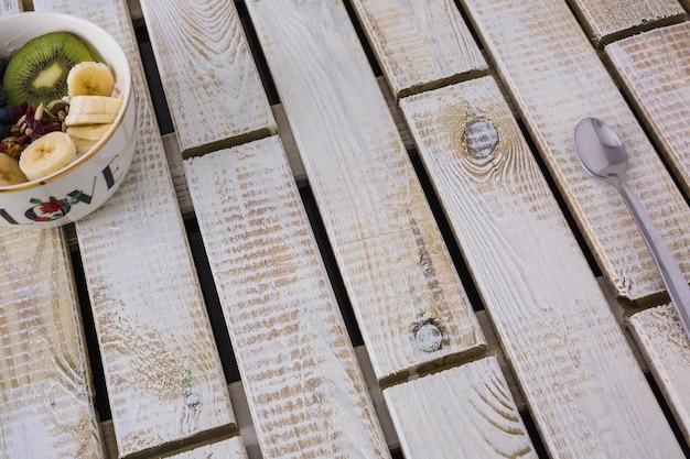 Kom van gezonde verse fruitsalade en lepel op houten achtergrond