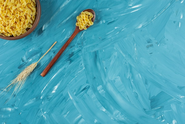 Kom van ongekookte droge macaroni die op marmeren achtergrond wordt geplaatst.
