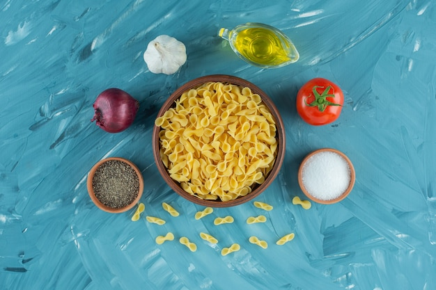 Kom van ongekookte droge macaroni en verse groenten op blauwe achtergrond.