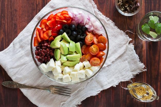 Kom van plantaardige salade met avocado en olijven