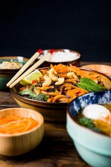 Kom van thaise udonnoedels met noten; broccoli; citroen en munt toppings