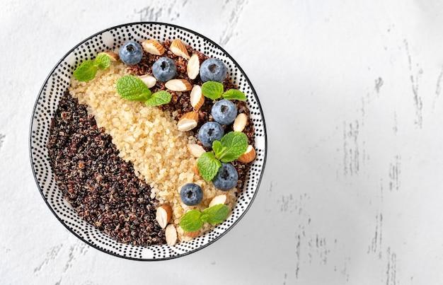 Kom van witte, rode en zwarte gekookte quinoa met noten en bosbessen
