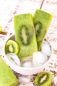 Kom vanille en kiwi yoghurt ijslollys op witte rustieke houten tafel