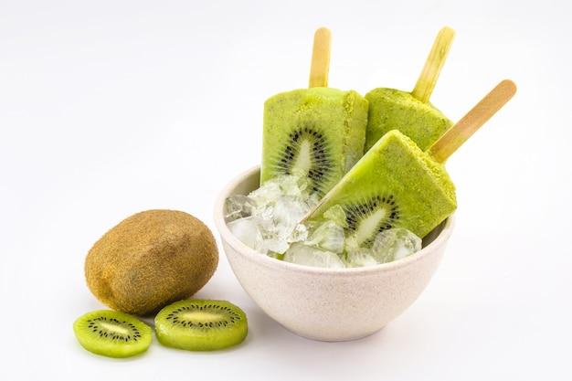 Kom vanille en kiwi yoghurtijslollys op wit