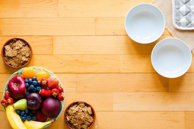 Kom vers fruit met banaan, appel, aardbeien, abrikozen, bosbessen, pruimen, volle granen, vorken, bovenaanzicht