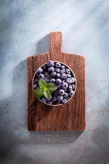 Kom verse bosbessen op rustieke houten bord. biologisch voedsel, bosbessen en muntblad voor een gezonde levensstijl.